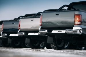 Back view of row of pickup trucks showing legal tail lights.