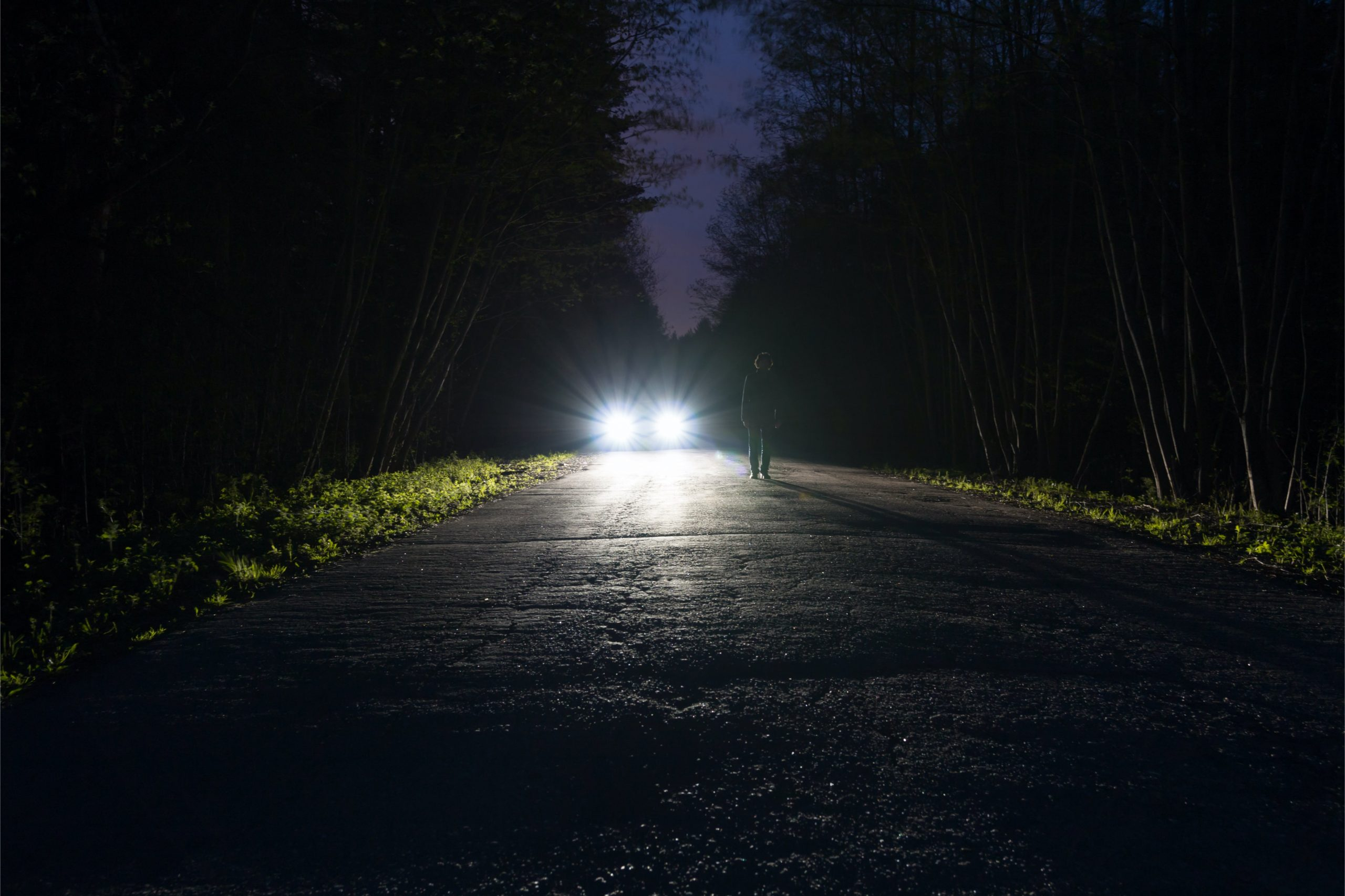 Front view of headlight beams in the distant at night on a dark road.