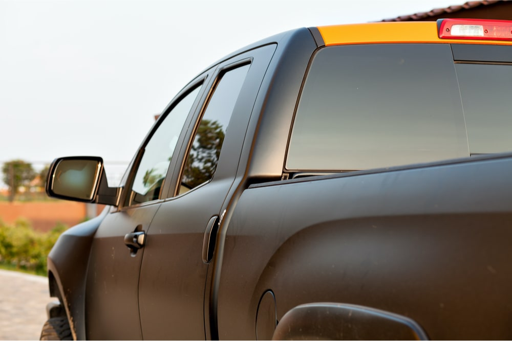 Rear/Side view of a matte black pickup truck, with third brake light visible.