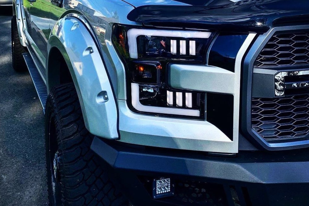 Close up picture of one cool looking headlight on a white SUV.